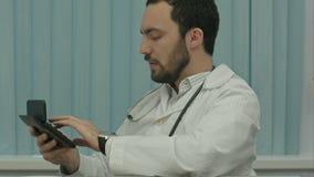 Ernster männlicher Doktorfokus auf Kostenberechnung stock footage