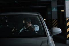ernster männlicher privater Detektiv in der Sonnenbrille, die im Auto sitzt stockfoto