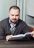 Ernster männlicher Student, der eine Buchbibliothek liest Stockfotografie