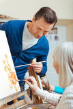 Ernster Mann, der ältere Frau in der Malereischule unterrichtet Lizenzfreie Stockfotografie