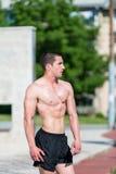 Ernster Mann, der draußen steht und Muskeln biegt Stockbilder