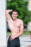 Ernster Mann, der draußen steht und Muskeln biegt Stockbild