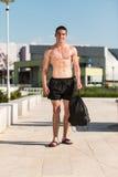 Ernster Mann, der draußen steht und Muskeln biegt Lizenzfreies Stockfoto