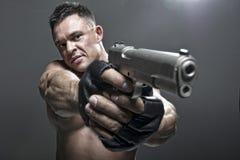 Ernster Mann, der ein Gewehr hält Stockbilder