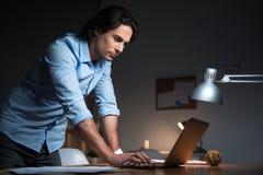 Ernster Mann, der an einem Laptop arbeitet stockbild