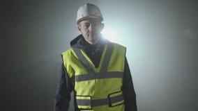 Ernster Mann in der Erbaueruniform und -sturzhelm kommt n?her an der Kamera vor schwarzem Hintergrund mit Scheinwerfer stock video