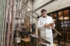 Ernster Mann, der Ergebnisse an der Bierfabrik merkt Stockbilder