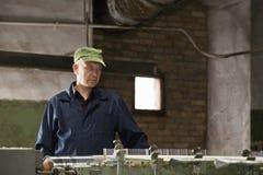 Ernster Mann in der grünen Kappe an der Maschine stockfoto