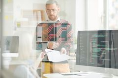 Ernster Mann, der Papiere mit Code zu Damenprogrammierer gibt lizenzfreie stockfotografie