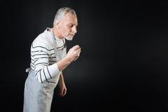 Ernster Mann, der seine rechte Biegung im Ellbogen hält Stockfotografie