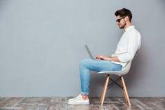 Ernster Mann in der Sonnenbrille, die auf Stuhl sitzt und Laptop verwendet Stockfotos