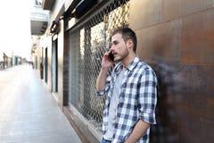 Ernster Mann, der am Telefon im sreet einer alten Stadt spricht lizenzfreie stockfotos