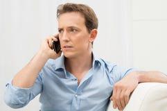 Ernster Mann, der am Telefon spricht Stockbilder