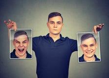 Ernster Mann, der zwei verschiedene Gesichtsgefühlmasken von hält stockbild