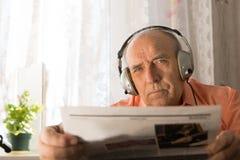 Ernster Mann des hohen Alters mit dem Kopfhörer, der Zeitung hält Lizenzfreie Stockfotos