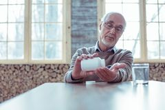 Ernster Mann im Ruhestand, der entlang der Flasche mit Medizin anstarrt stockbilder