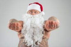 Ernster Mann mit den Tätowierungen, die Weihnachtshut und -bart tragen