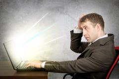 Ernster Mann sitzt bei Tisch und schreibend auf Laptop Stockbild