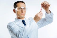 Ernster medizinischer Wissenschaftler mit der Blutprobe, die Kamera untersucht Lizenzfreie Stockfotografie