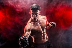 Ernster muskulöser Kämpfer, der den Durchschlag mit den Ketten geflochten über seiner Faust tut Stockfotografie