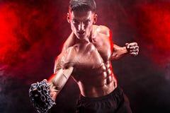 Ernster muskulöser Kämpfer, der den Durchschlag mit den Ketten geflochten über seiner Faust tut Stockfotos