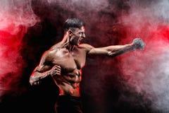 Ernster muskulöser Kämpfer, der den Durchschlag mit den Ketten geflochten über seiner Faust tut Stockbild