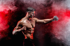 Ernster muskulöser Kämpfer, der den Durchschlag mit den Ketten geflochten über seiner Faust tut Lizenzfreie Stockfotos