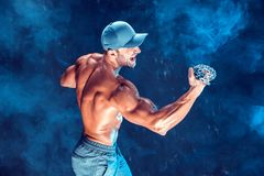 Ernster muskulöser Kämpfer, der den Durchschlag mit den Ketten geflochten über seiner Faust im Rauche tut Stockfotos