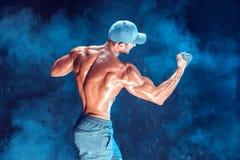 Ernster muskulöser Kämpfer, der den Durchschlag mit den Ketten geflochten über seiner Faust im Rauche tut Lizenzfreie Stockbilder