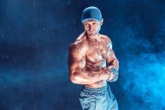 Ernster muskulöser Kämpfer, der den Durchschlag mit den Ketten geflochten über seiner Faust im Rauche tut Lizenzfreies Stockbild