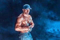 Ernster muskulöser Kämpfer, der den Durchschlag mit den Ketten geflochten über seiner Faust im Rauche tut Stockbilder