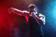 Ernster muskulöser Kämpfer, der den Durchschlag mit den Ketten geflochten über seiner Faust tut Lizenzfreie Stockbilder