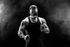 Ernster muskulöser Kämpfer, der den Durchschlag mit den Ketten geflochten über seiner Faust tut Lizenzfreies Stockbild