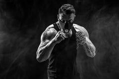 Ernster muskulöser Kämpfer, der den Durchschlag mit den Ketten geflochten über seiner Faust tut Lizenzfreie Stockfotografie