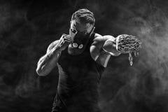 Ernster muskulöser Kämpfer, der den Durchschlag mit den Ketten geflochten über seiner Faust tut Stockbilder