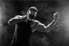 Ernster muskulöser Kämpfer, der den Durchschlag mit den Ketten geflochten über seiner Faust tut Lizenzfreies Stockfoto