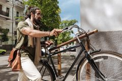 Ernster netter Mann, der sein Fahrrad hält Stockfoto