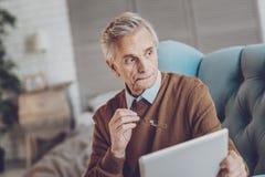 Ernster Pensionär, der in den Gedanken tief ist stockbilder