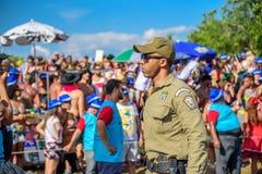Ernster Polizist des städtischen Schutzes in der Sonnenbrille, die während Bloco Orquestra Voadora, Carnaval 2017 arbeitet Lizenzfreie Stockfotografie