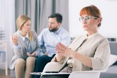 Ernster Psychologe, der ein Handzeichen macht, während ein verheiratetes Paar im Hintergrund spricht stockbilder