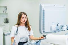 Ernster, starker junger Doktor, Spezialist, der Ultraschalldiagnostik-Maschine für pacient Prüfung verwendet Kopieren Sie Platz S lizenzfreies stockbild