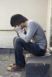 Ernster stattlicher Mann, der ein auf der Türstufe sitzt. lizenzfreies stockbild