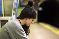Ernster tragender Hut der jungen Frau Woll, sitzend an der Untertageplattform Stockfotos