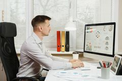Ernster und verfasster (sentence Geschäftsmann im Hemd, das am Schreibtisch, arbeitend am Computer mit modernem Monitor sitzt Man lizenzfreie stockfotografie