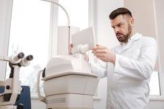 Ernster verwirrter Augenarzt, der den Monitor betrachtet Lizenzfreie Stockfotografie