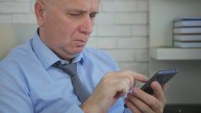Ernster Wirtschaftler im Büro-Raum-Text unter Verwendung des Handys stockfoto