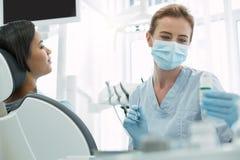 Ernster Zahnarzt, der ein Instrument hält Stockbilder