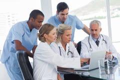 Ernstes Ärzteteam, das einen Laptop verwendet Lizenzfreies Stockfoto