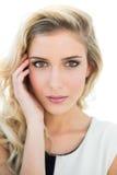 Ernstes attraktives blondes Modell, das ihren Tempel berührt Stockfotos