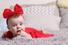 Ernstes Baby im roten Kleid und im Bogen Lizenzfreie Stockfotos